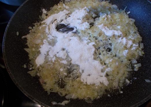 Zwiebel und Knoblauch in Pfanne anschwitzen, mehlieren. Normalerweise werden hier die Speckwürfel gleich mitgebraten.  TIPP: Falls Vegetarier/innen mitessen, den Speck separat anbraten und extra anbieten