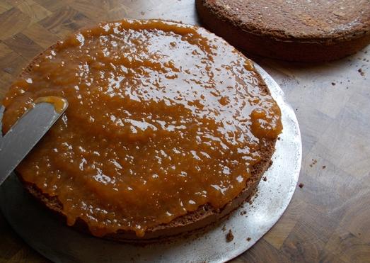 Torte in der Mitte sauber durchschneiden, dann den unteren Teil mit Marillenmarmelade bestreichen..