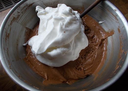 Die Hälfte des Schnees unter die Schokoladen-Masse heben, verrühren, dann das Mehl unterheben, weiterrühren und schließlich mit dem untergehobenen Schneerest fertig rühren.