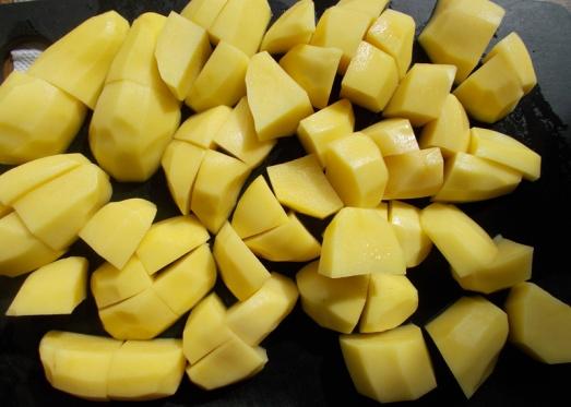 Festkochende Kartoffeln grob würfelig schneiden, Zwiebel fein schneiden.
