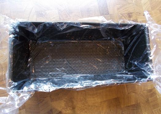 Kastenform etwas einölen und  mit Klarsichtfolie auslegen (durch das Öl hält die Folie besser).