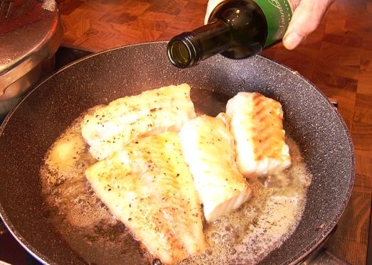 ... mit Weißwein aufgießen, zudecken und auf sehr kleiner Flamme ziehen lassen.