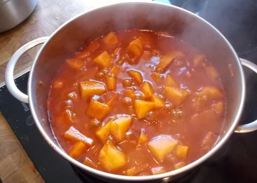 Die Kartoffeln sollten leicht mit Flüssigkeit bedeckt sein, also eventuell etwas Wasser nachgießen. Zudecken, köcheln lassen.