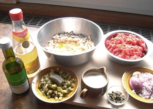 Zutaten: Faschiertes (gemischtes Rinder- und Schweinehackfleisch), Knödelbrot, Eier, gehackter Zwiebel, Senf, Salz, Pfeffer, Öl, gehackter Zwiebel, würfelig geschnittene Essiggurkerl, gehackte Kapern, Essig, Weißwein, Obers