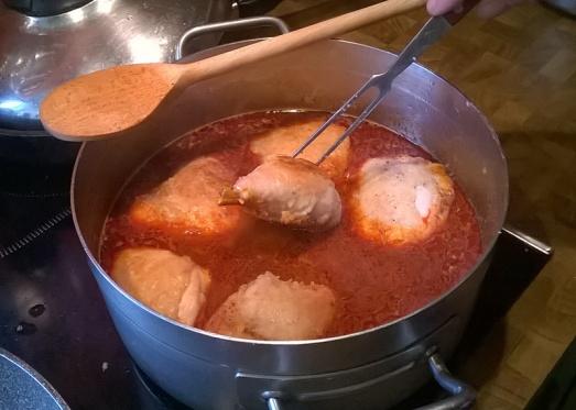 Die angebratenen Hühnerteile in die Paprikasauce legen und zugedeckt 15 Minuten köcheln lassen.