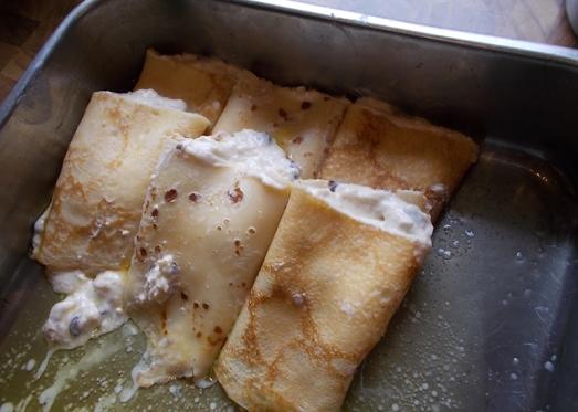 ... und in die mit flüssiger Butter vorbereitete Form schlichten, dabei durch die Butter ziehen (siehe Video!) Idealerweise steht die Form leicht schräg, damit sich die Butter an einem Ende sammelt.
