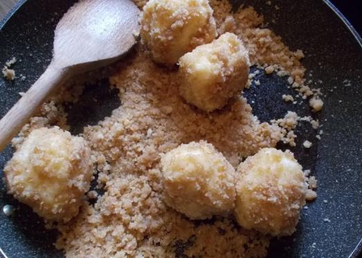 Die gekochten Knödel in der Brösel-Mischung wälzen.