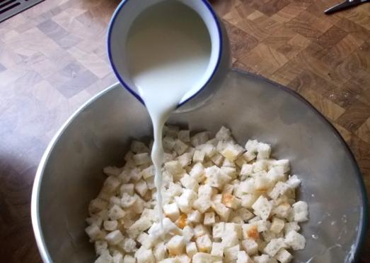 Semmeln würfelig schneiden und in etwas Milch einweichen.