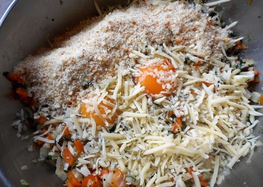 Den blanchierten Blattspinat durchhacken und noch etwas mit den Zwiebeln anrösten lassen, bevor man alles unter das blanchierte Gemüse mischt. Eier dazugeben (hier gezeigte Menge: zwei Eier), Semmelbrösel (hier: drei gut gehäufte EL), geriebenen Käse und das gehackte Petersiliengrün.